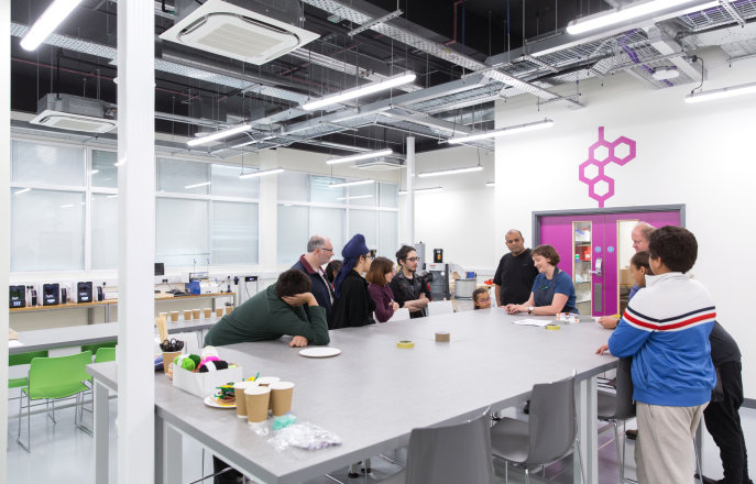 People gather around a table at the Imperial College Makerspace