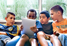 Four boys sitting on a beanbag staring at tablet screen