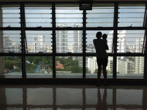 Parent holds their child looking out a window into the cityscape