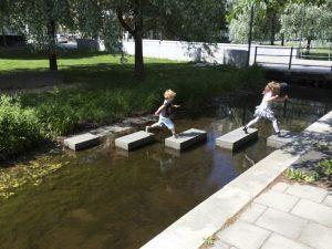 Kids jumping on rocks across water