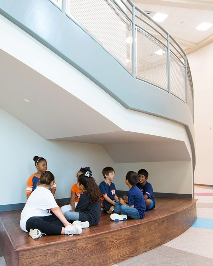 Students sitting under staircase inside Library inside Jim and Pam Wells Elementary School in Cypress